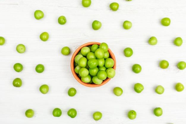 하얀 나무에 손수 만든 그릇에 흩어져 녹색 매. 평면도.