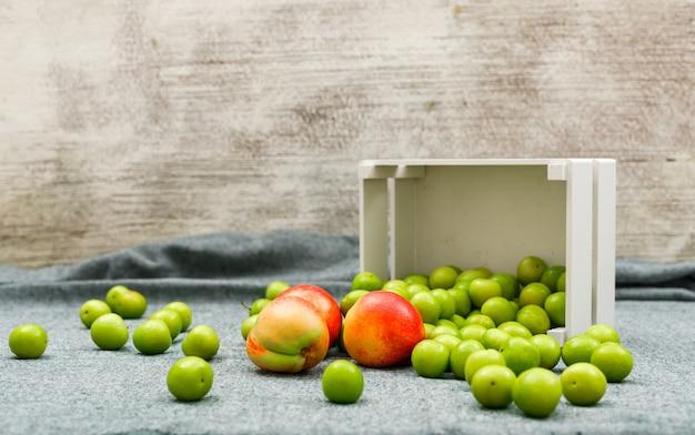 白い長方形のボウルに散りばめられた緑の梅とグレーと汚れたおいしい桃の側面図