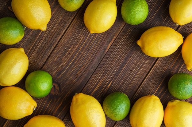 Scattered lemons with limes flat lay on a wooden table