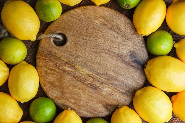 Scattered lemons with limes on wooden and cutting board, flat lay.