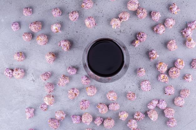 대리석 배경에 차가운 콜라 잔을 둘러싼 설탕에 절인 팝콘 덩어리가 흩어져 있습니다. 고품질 사진