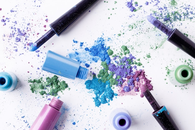 Scattered multicolored eyeshadow with brushes and tube