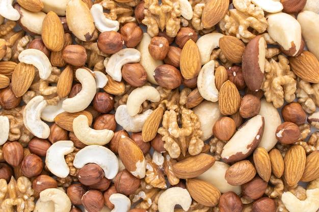 Разбросанные орехи на столе. фон орехов. фундук, грецкие орехи, миндаль, бразильские орехи и кешью.