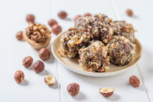 На белом столе разбросаны орехи и сладости из тертых орехов и сухофруктов на белом столе. вкусные свежие домашние конфеты.