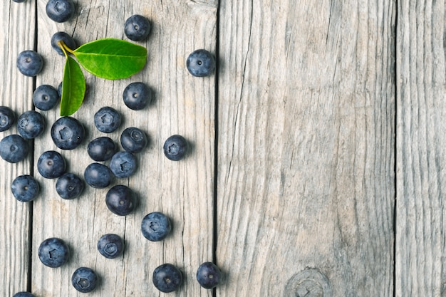 Scattered organic blueberries with leaves on wooden background