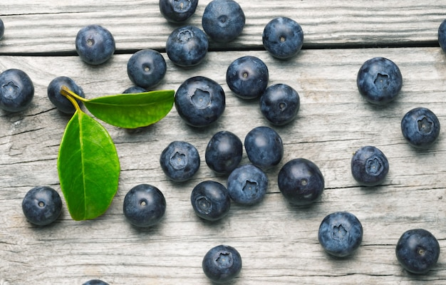 Scattered organic blueberries on wooden background with leaves close up