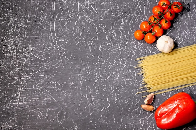 Scattered pasta, garlic, tomatoes, on grey background