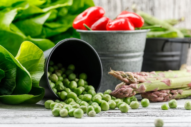 Scattered peas with lettuce, green pods, asparagus, peppers from a bucket on wooden wall, side view.