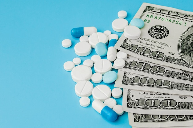 Scattered pharmaceutical medicine pills, tablets and capsules on dollar money