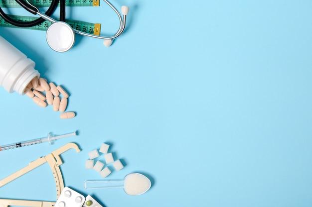 散らばった薬の丸薬、錠剤の水ぶくれ、インスリン注射器、聴診器、キャリパー、巻尺、青い背景に精製された砂糖、コピースペース。 11月14日、糖尿病啓発デー。フラットレイ