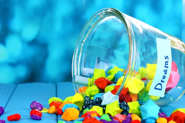 青い背景の上の青い木製のテーブルの上のガラスの花瓶の夢と紙と色の石の散らばった部分