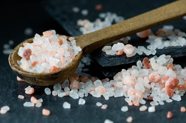 Scattered pink himalayan salt and wooden spoon, health, wellness concept.