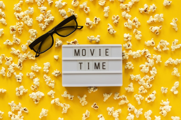 Scattered popcorn, 3d glasses and lightbox text movie time. top view template