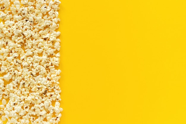 Scattered popcorn border left edge and empty space on yellow paper background.