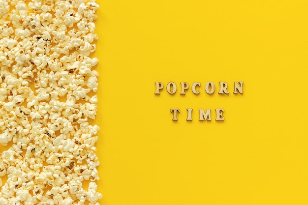 Scattered popcorn border left edge and popcorn time on yellow paper background.