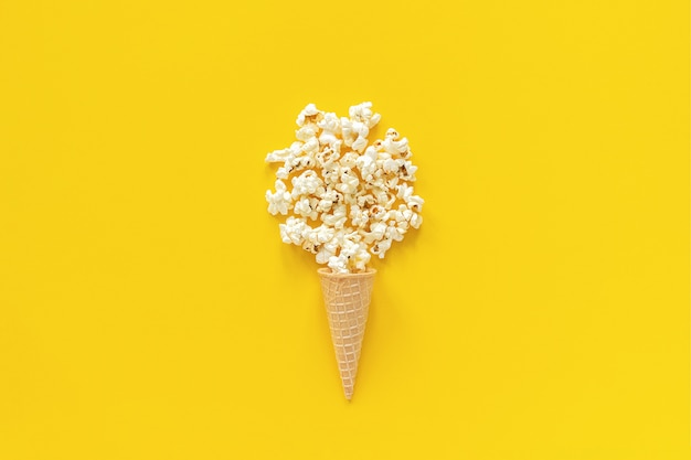 Scattered popcorn in ice cream waffle cone on yellow background