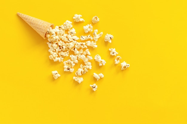 Scattered popcorn in ice cream waffle cone on yellow paper background