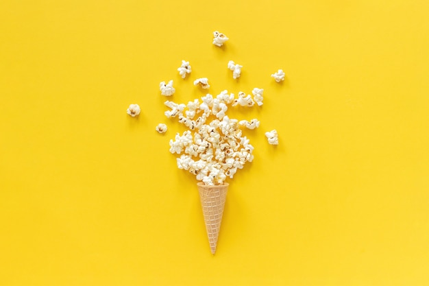 Scattered popcorn in ice cream waffle cone on yellow paper background.