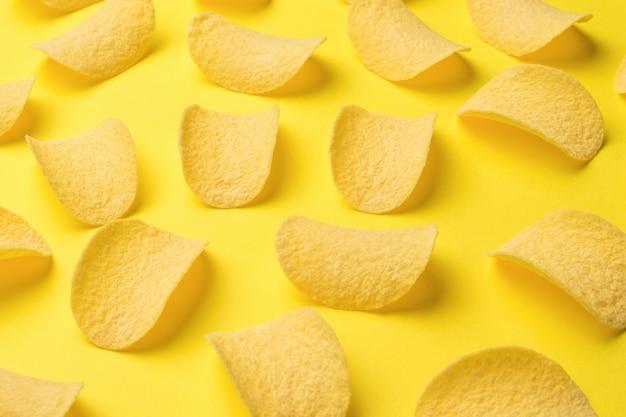 밝은 노란색 배경에 흩어져 있는 감자 칩. 인기있는 감자 요리.