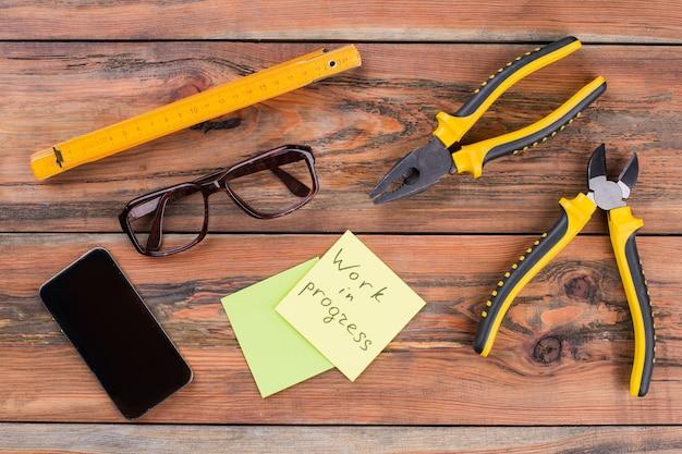 Разбросаны профессиональные инструменты для деревообработки, металлообработки и смартфона