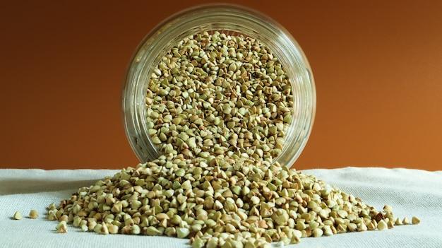 Рассыпаем сырую зеленую гречку стеклянной банкой для круп. концепция веганских органических продуктов питания.