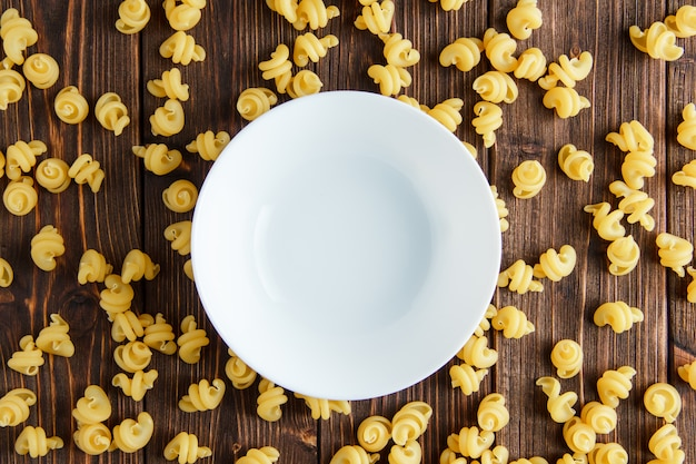 Разбросанные сырые макароны с пустой тарелкой лежат на деревянном столе