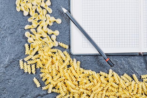 ノートと鉛筆の周りに生のパスタが散らばっています。