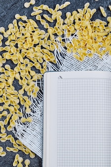 Scattered raw pastas around notebook and white tablecloth.