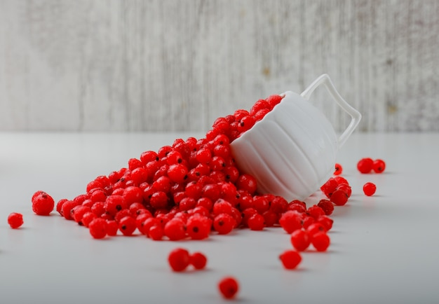 Scattered red currants in a white cup.