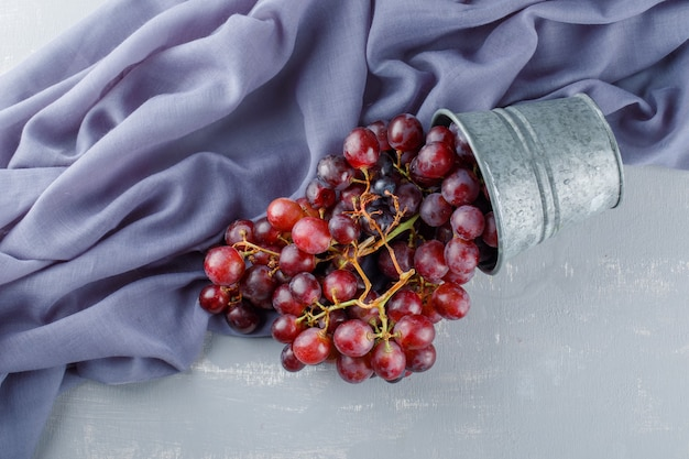 Разбросанный красный виноград из мини-ведра по гипсу и текстилю,
