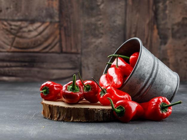 Рассеянные красные перцы из мини-ведра с деревянным куском на серой и каменной стене