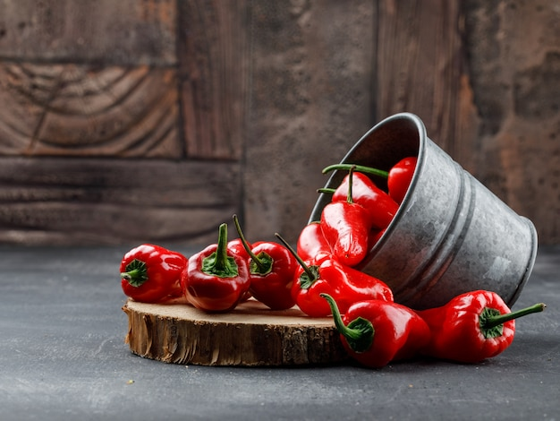 Scattered red peppers from a mini bucket with wooden piece side view on grey and stone tile wall