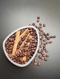Разбросанные жареные кофейные зерна и чаша кофе на черном