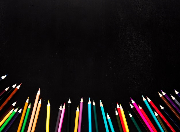 Scattered sharpened color pencils placed in bottom of black background