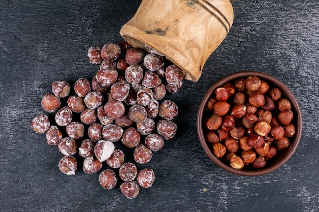 Scattered shelled hazelnuts in a brown bowl with wooden cup top view on a dark stone table
