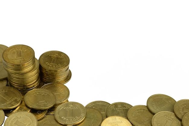 散らばった光沢のある黄色の鉄のコインと白い背景の上のスタック