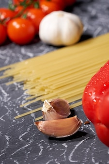 Scattered spaghetti garlic, tomatoes, on grey background