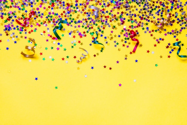 Scattered star shaped colorful glittering confetti and ribbons on yellow background. copy space.