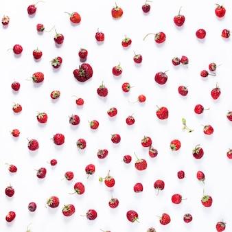 Разбросанная клубника изолированная на белизне. органическая ягода