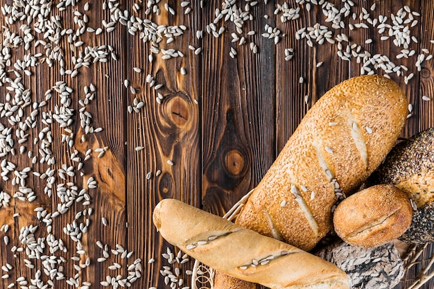 Scattered sunflower seeds and basket of breads on wooden background