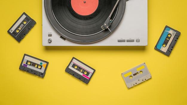 노란색 배경에 흩어져있는 테이프 카세트와 레코드 플레이어.