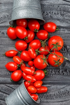 Scattered tomatoes from mini buckets flat lay on a grey wooden wall