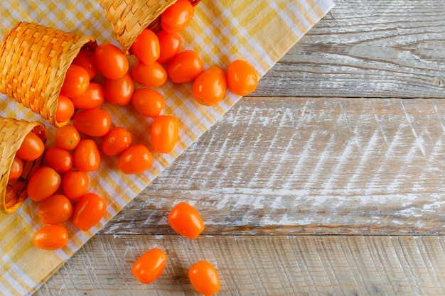 Scattered tomatoes from wicker baskets flat lay on picnic cloth and wooden table