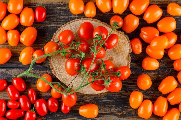나무와 커팅 보드에 흩어져 토마토. 평평하다.