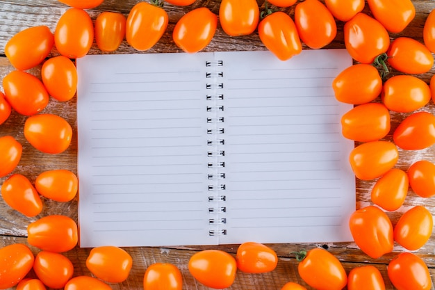 Scattered tomatoes with opened copybook on wooden table, flat lay.
