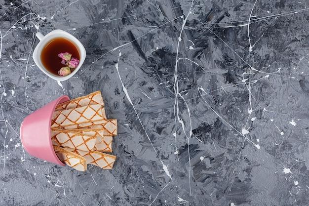 ハーブティーのカップと散らばったワッフルクッキー。
