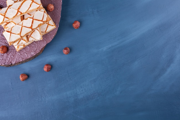 Scattered waffle cookies with hazelnuts placed on blue .