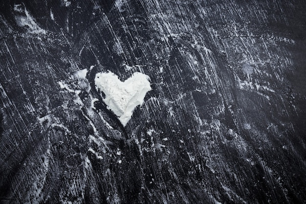 Scattered white flour with heart shape on black surface.