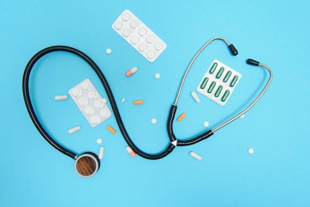 파란색 테이블에 흩어져있는 흰색 알약 의료, 약국 및 건강 관리 개념입니다. 의료 statoscope, 상위 뷰 파란색 배경 흰색 알 약.