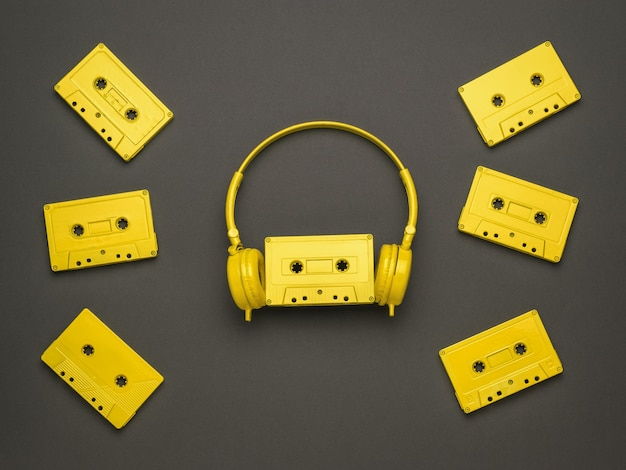 Scattered yellow tape cassettes and yellow headphones on a dark background. color trend. flat lay.
